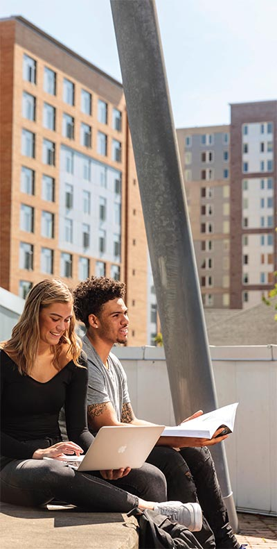 two students studying on the roof